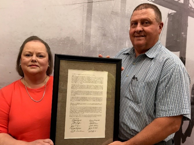 Faye Grisham Cosby receives the resolution honoring her late father, L.C. Grisham.