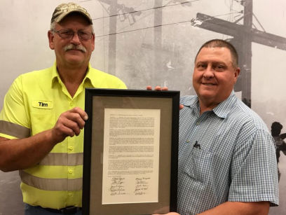 Tim Aldridge is presented with the resolution honoring his late father-in-law, L.C. Grisham.